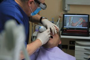 Dentist using an IOS intraoral scanner on a patient